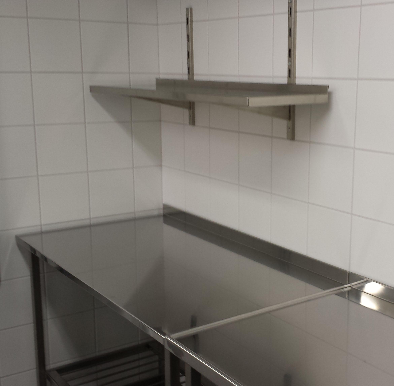 Arbetsbänk på stativ med gallerhylla och vägghylla ovan